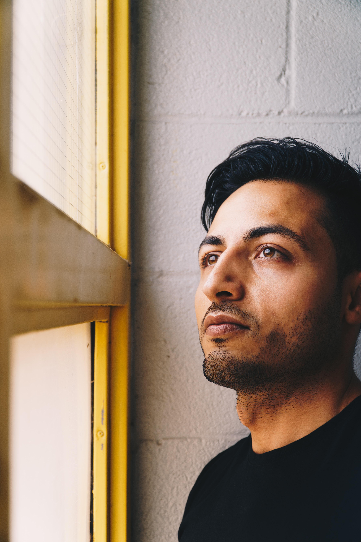 man looking on brown wooden sash window