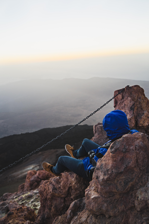 man sitting on cliff facing mountain