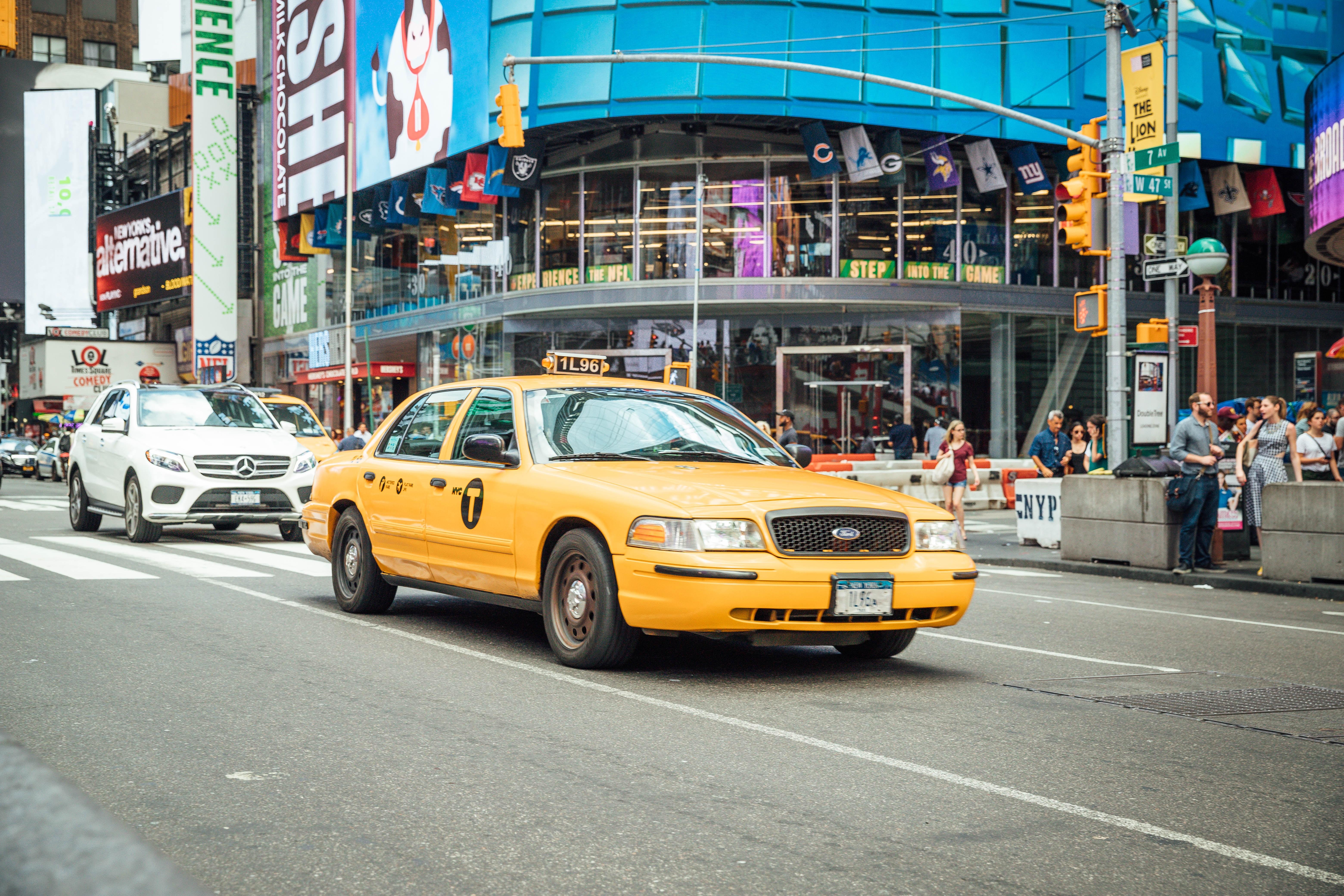 yellow taxi cab near white car