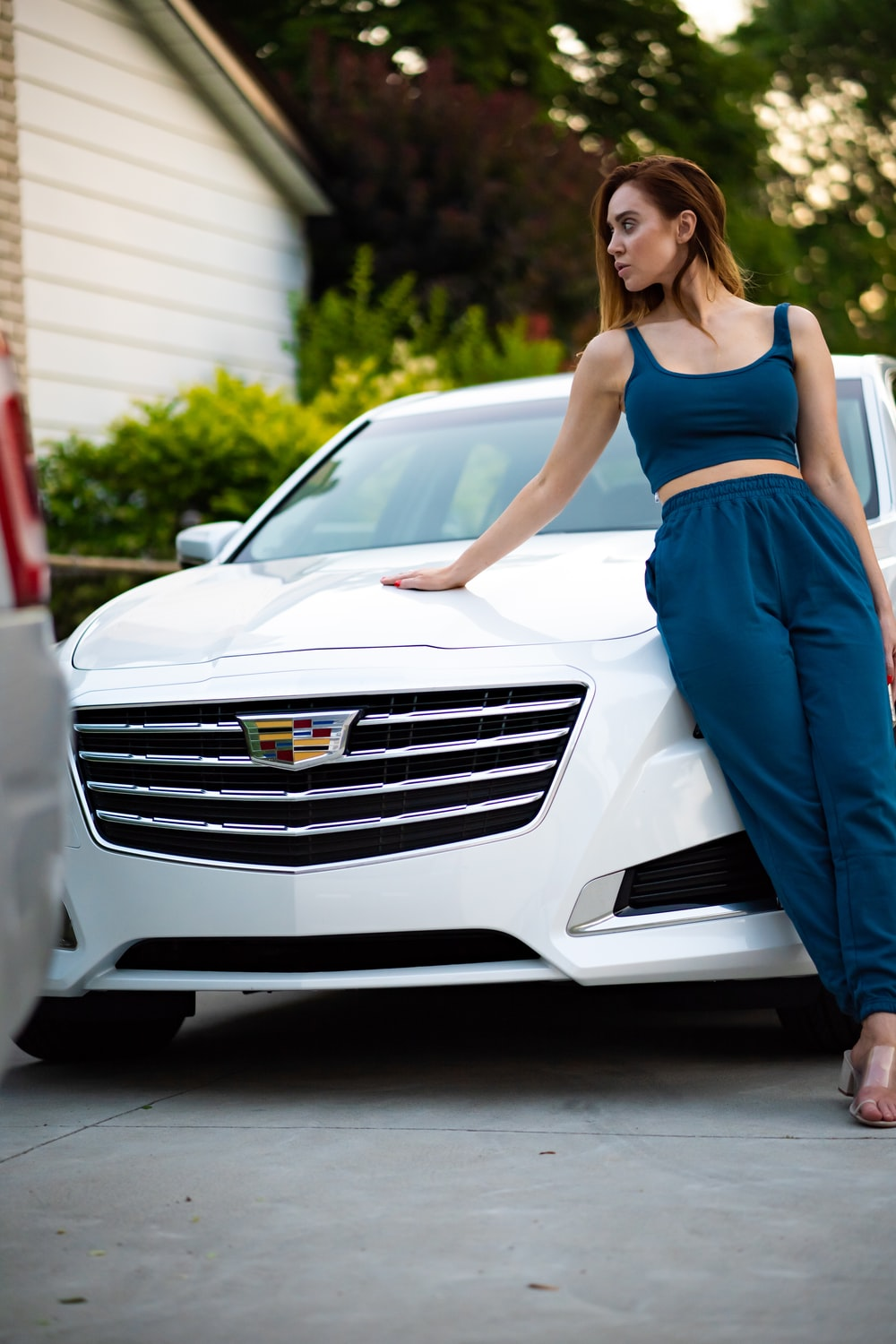 woman leaning on white Cadillac vehicle