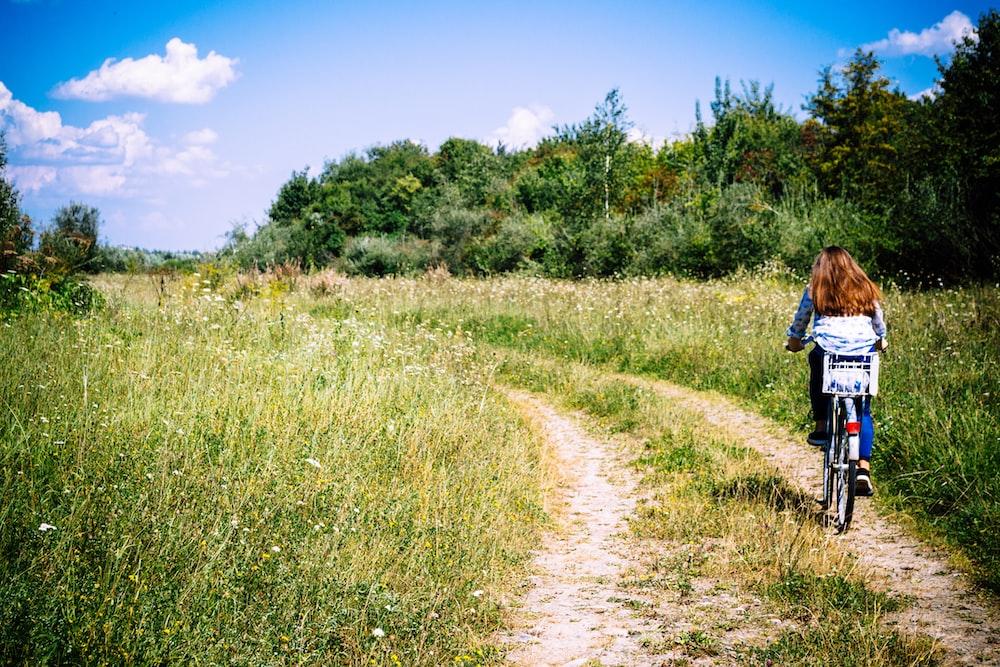 woman biking between grasses