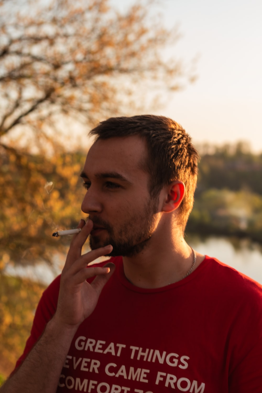 man standing smoking cigarette near body of water and trees