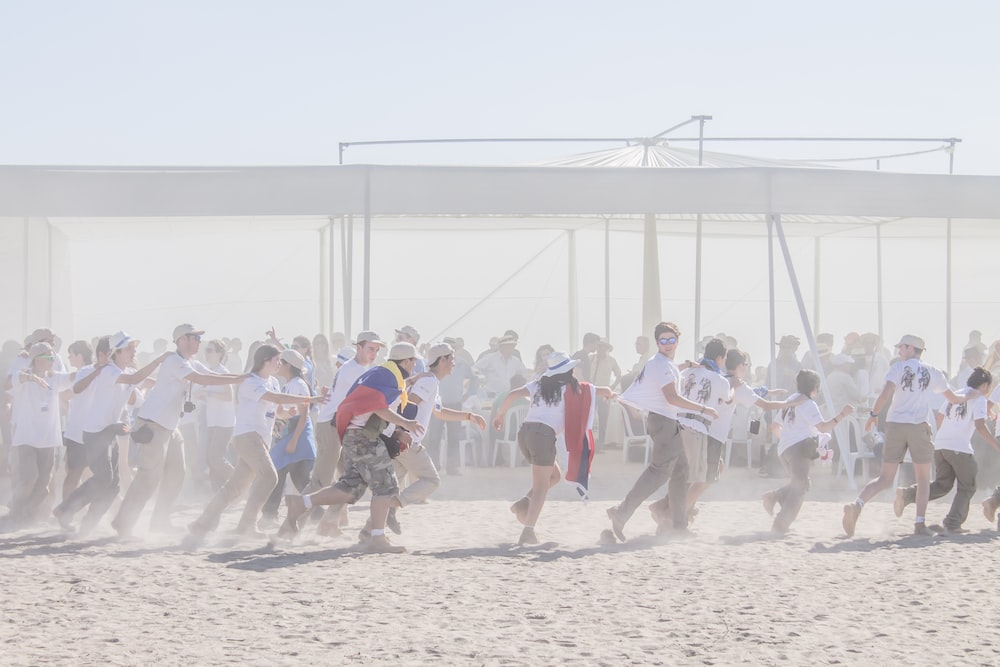 group of people running on sand ground