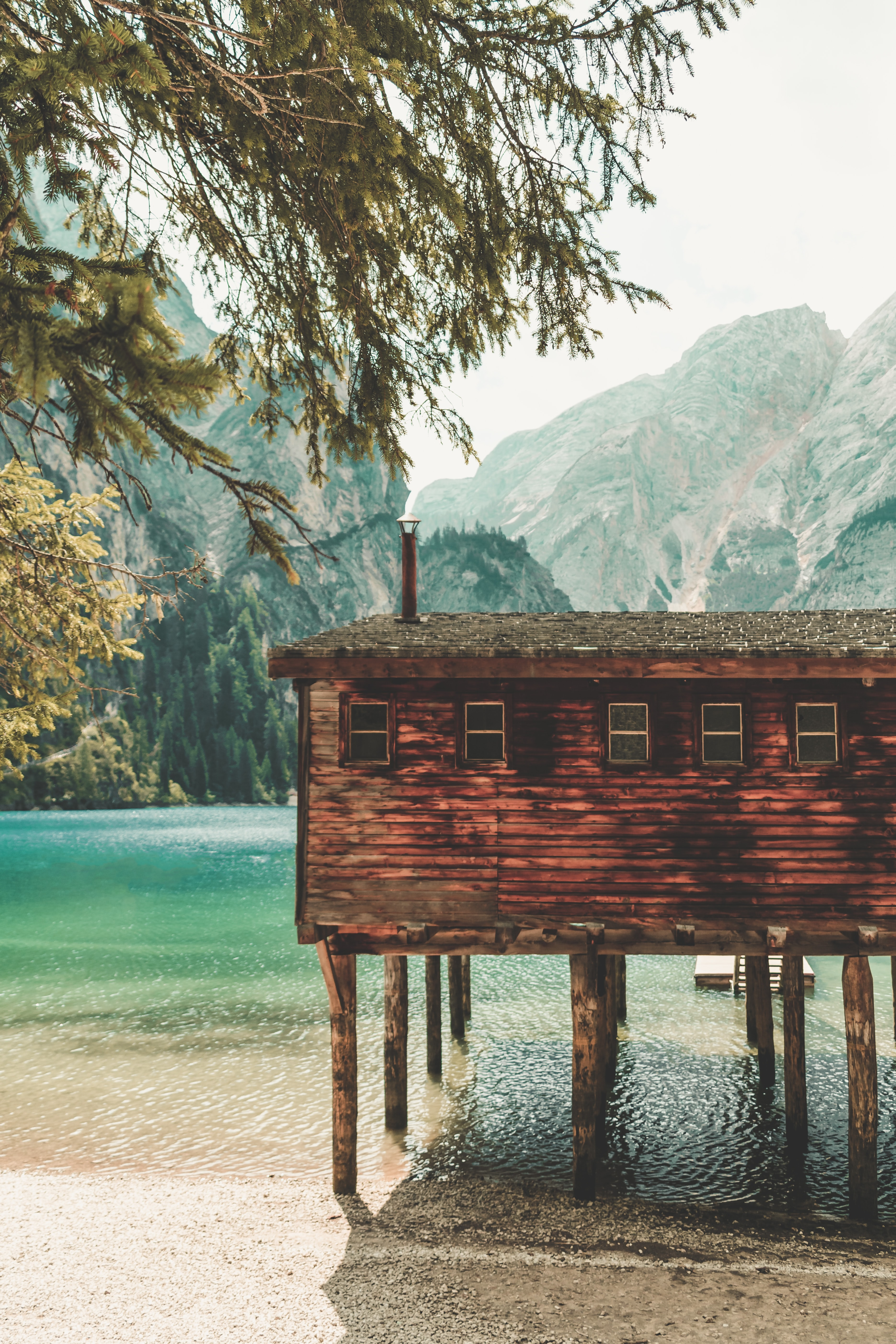 brown wooden house over sea surrounded with mountain