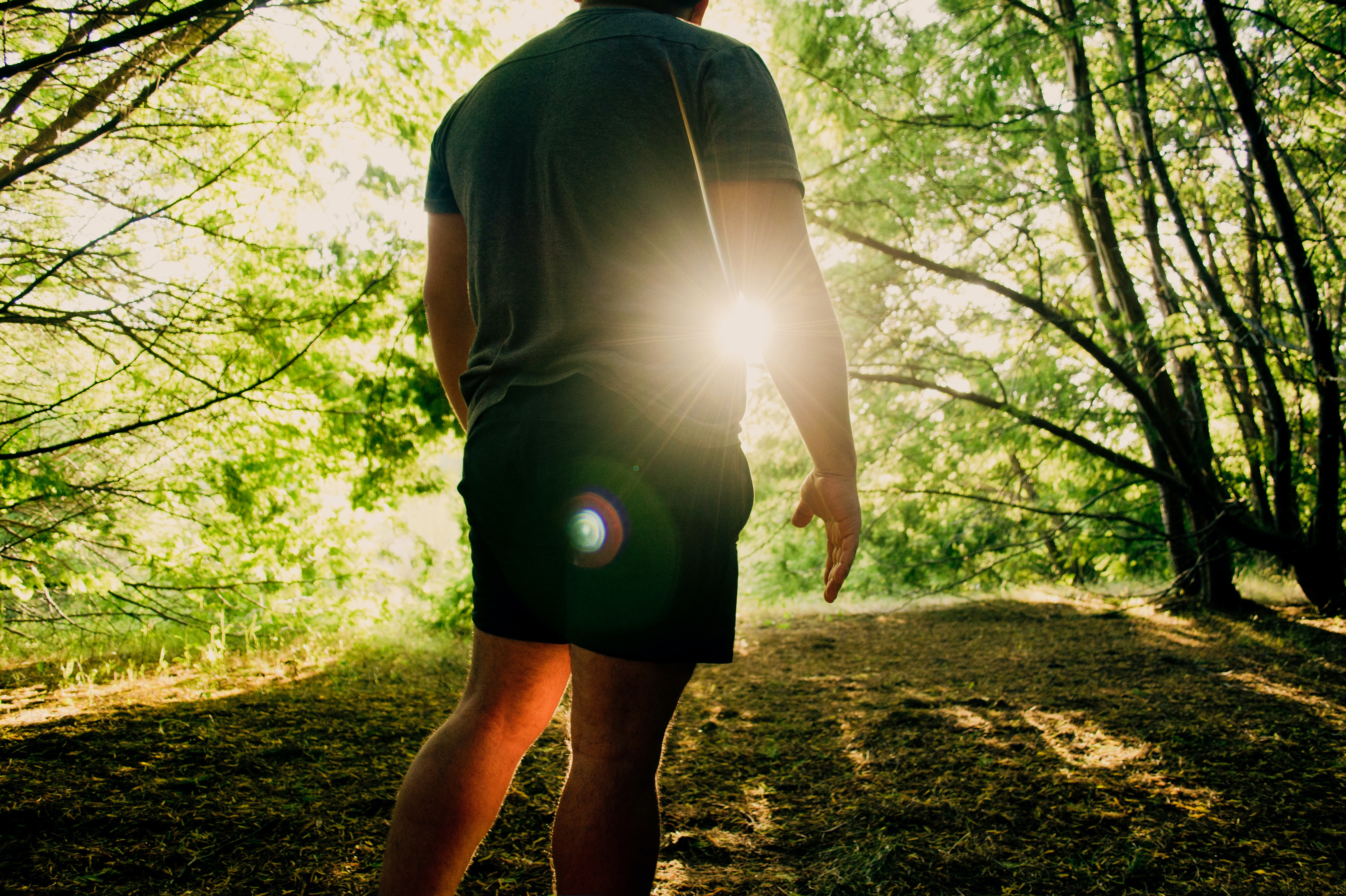 man standing on dirt path under green trees at daytime