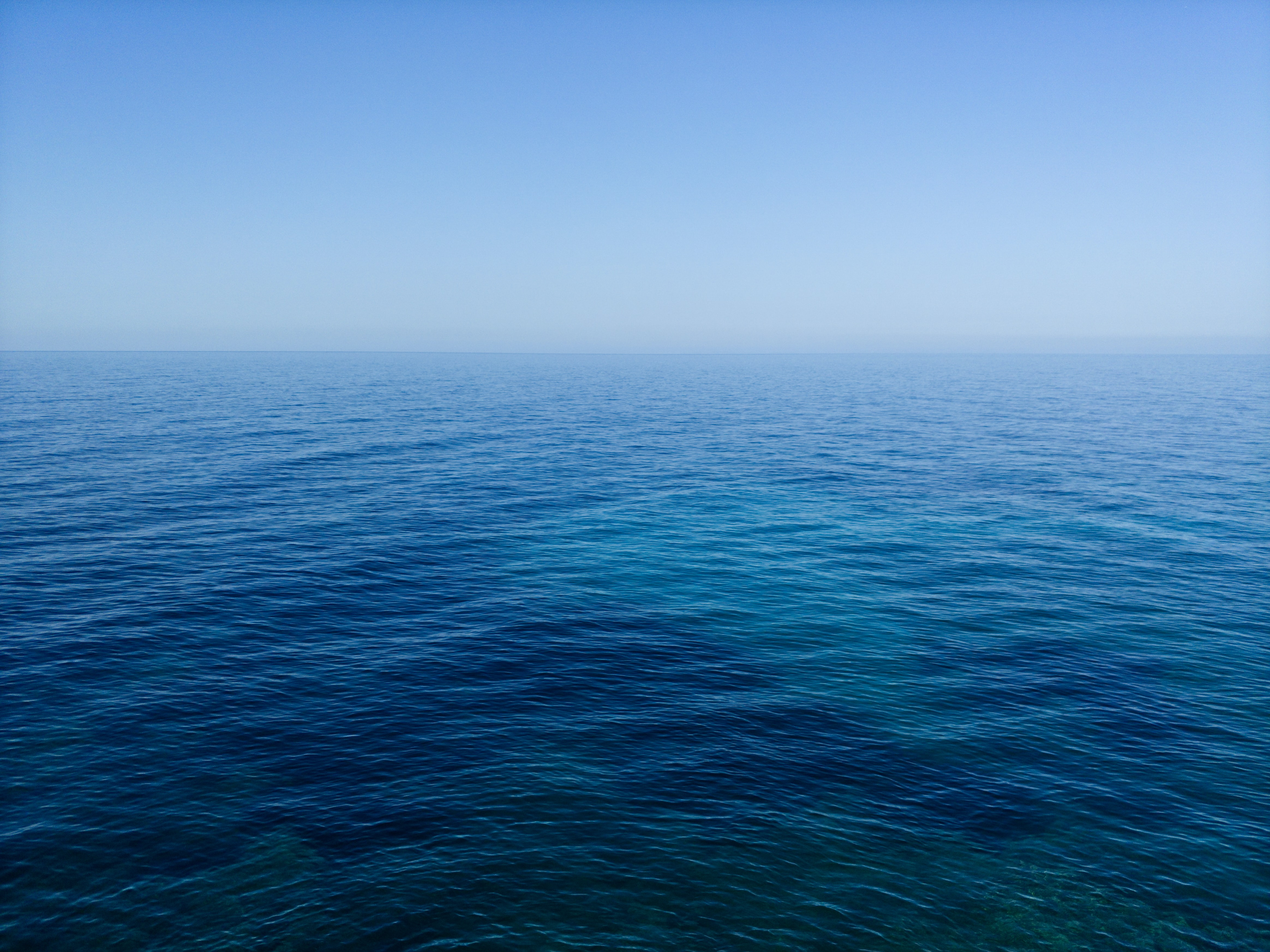 calm body of water under blue sky photography during daytime