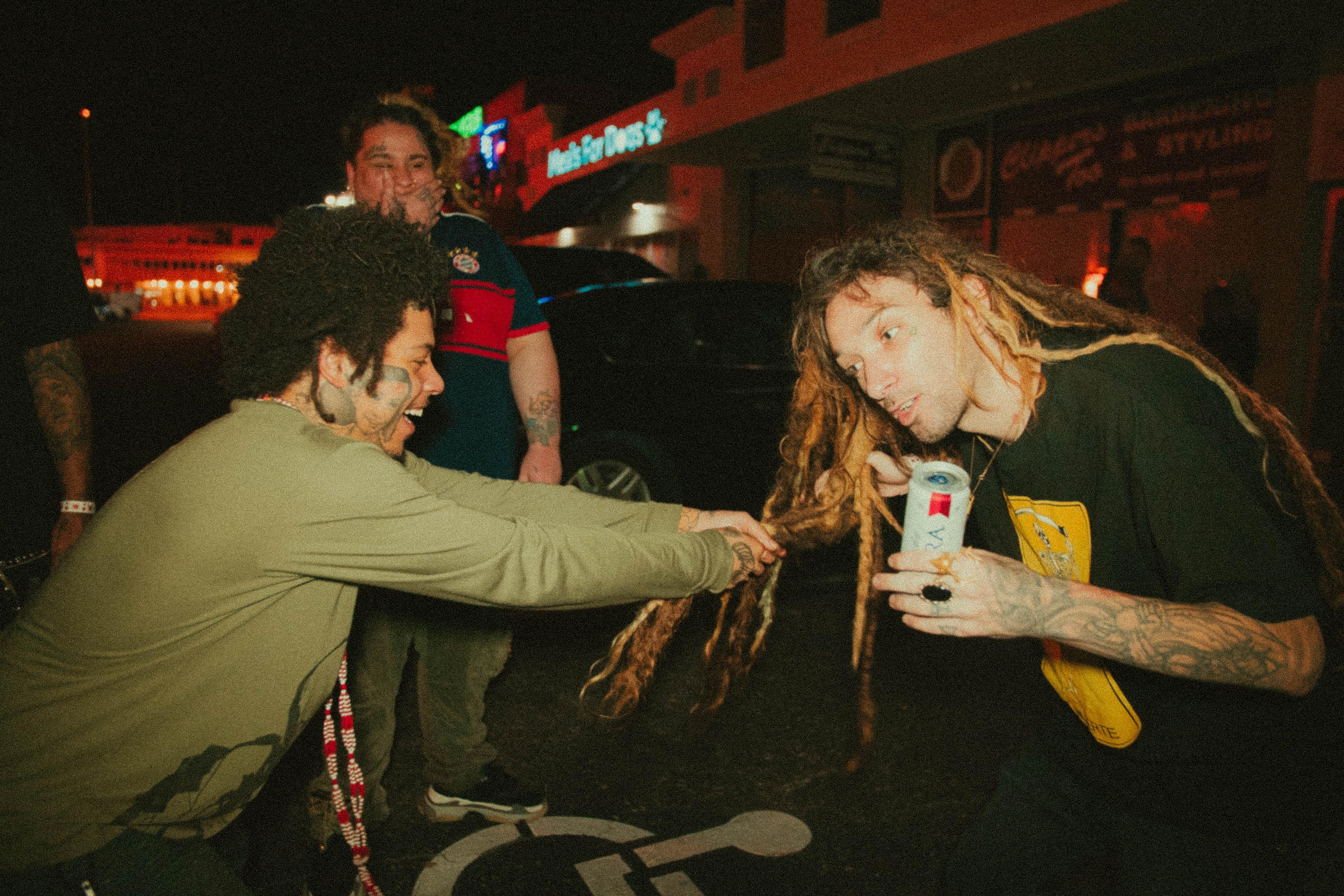 man holding hair dreadlocks hair of other man