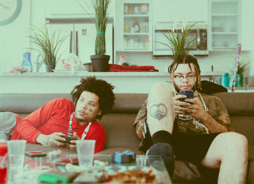 two men lying and sitting on brown sofa while holding game controller and using smartphone
