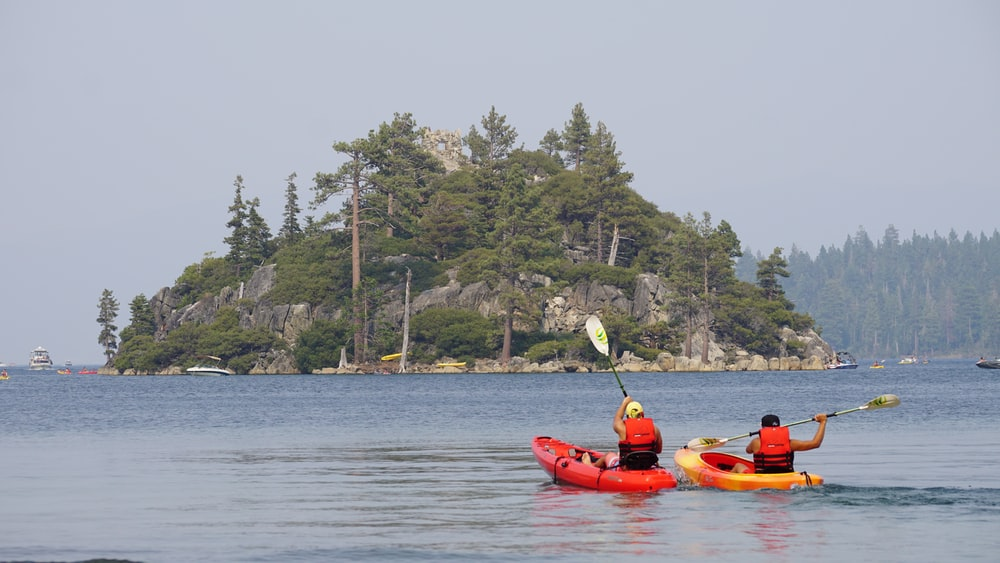 two person kayaking on water near islet