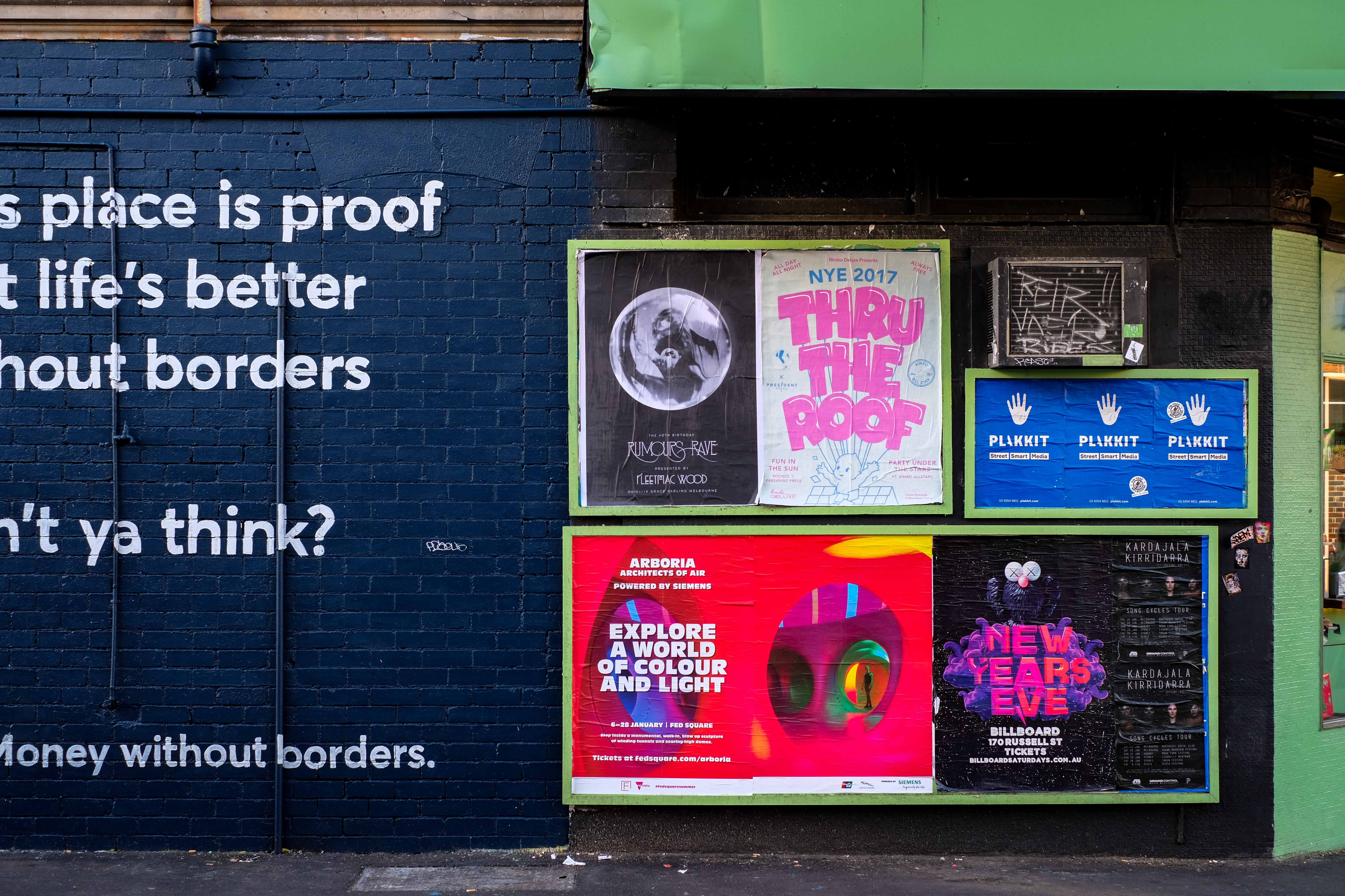posters mounted on building wall during daytime