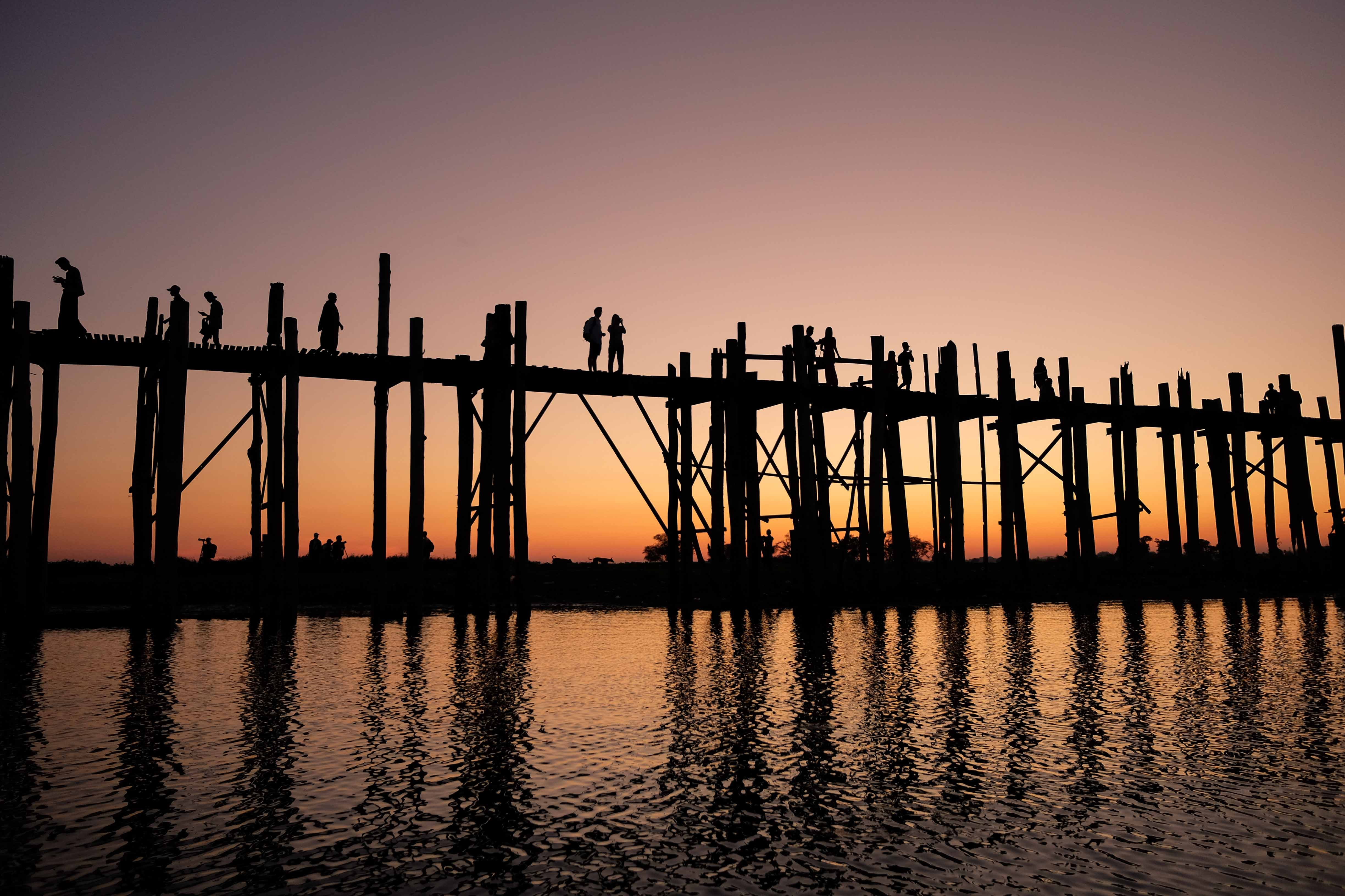 silhouette photograph of two person standing on wooden bridge during golden hour
