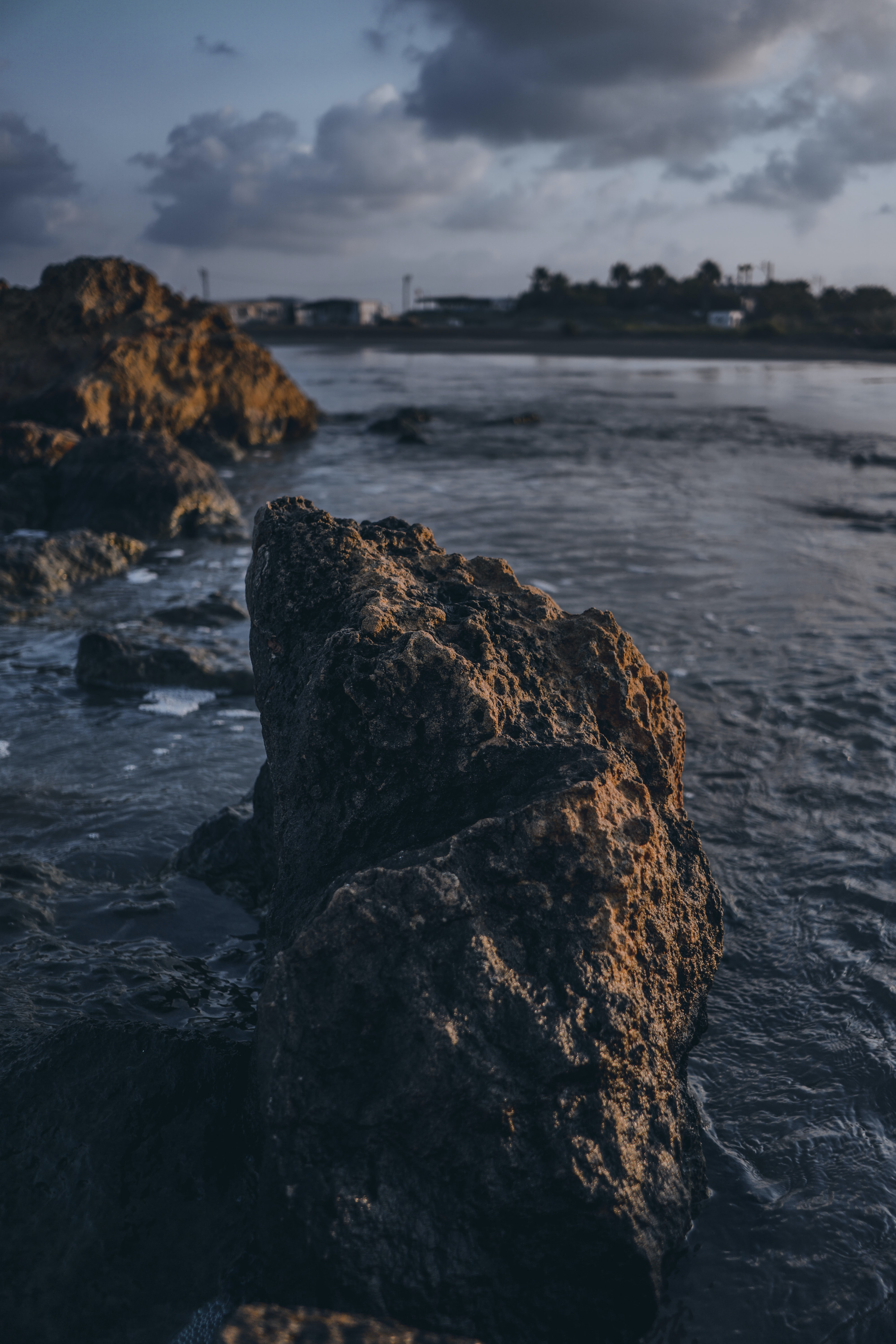 selective-focus photography of rock formation by body of water during daytime