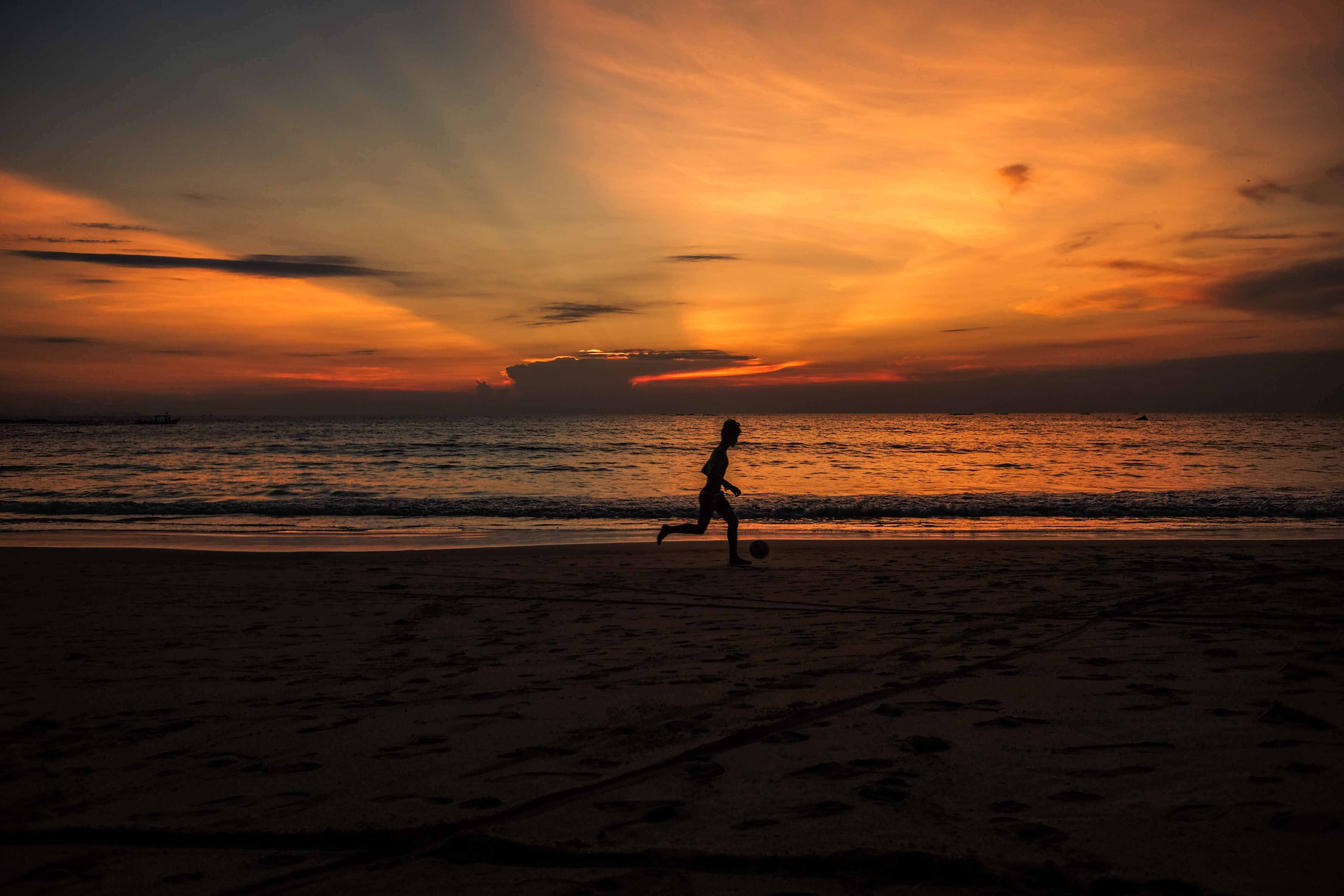 silhouette photo of person running near the shore