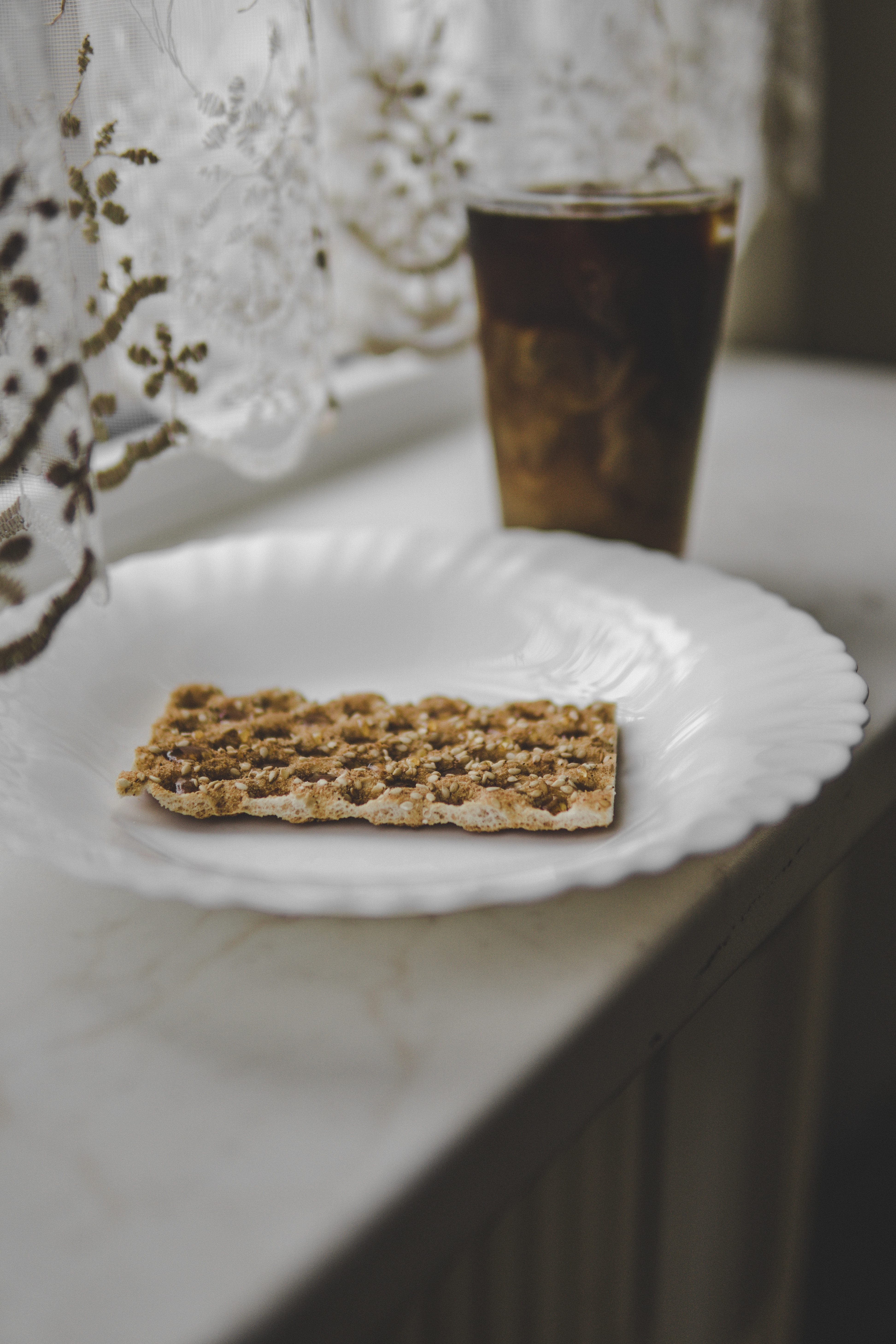 biscuit on round white ceramic plate near full drinking cup with brown liquid