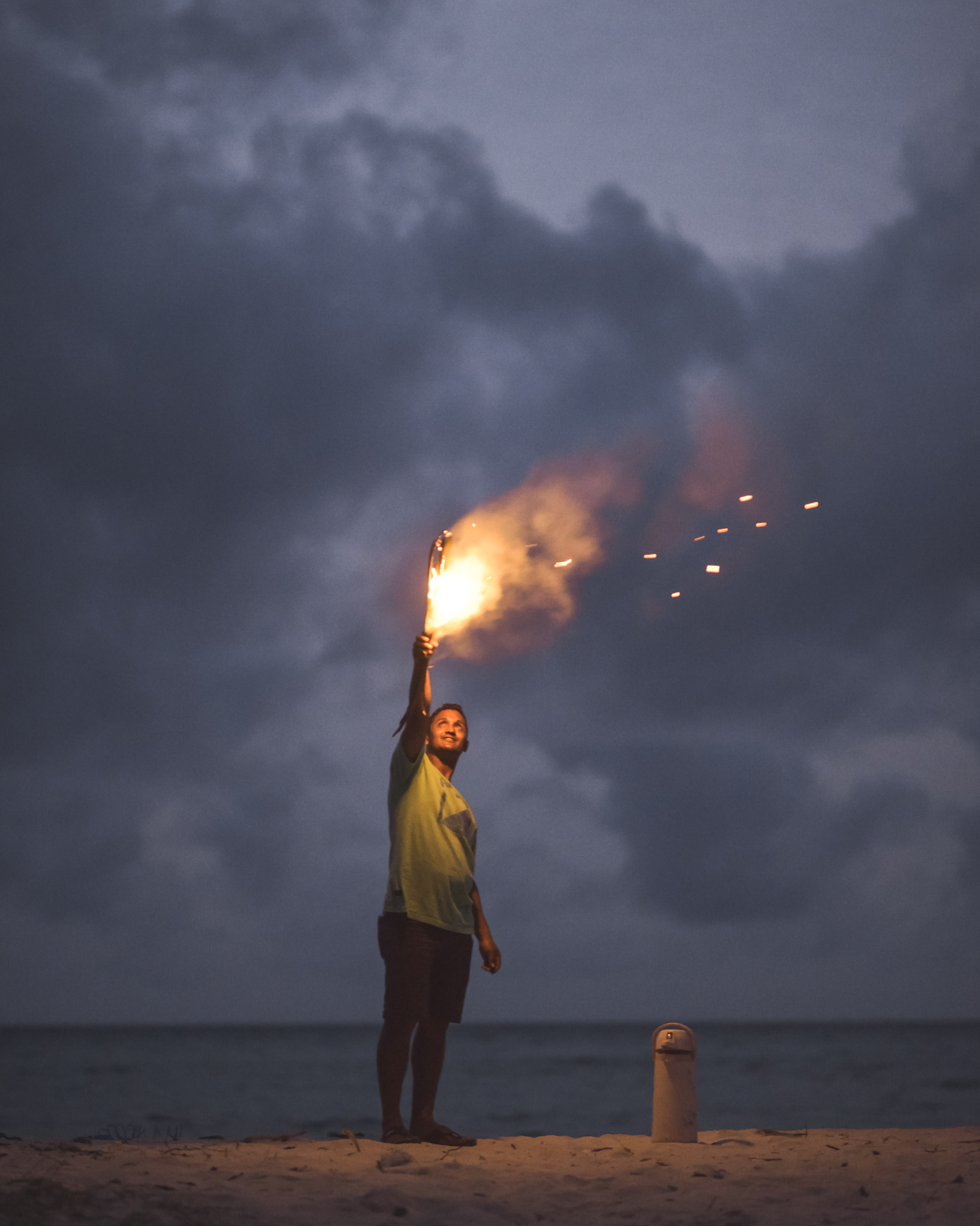 man holding torch on white sand