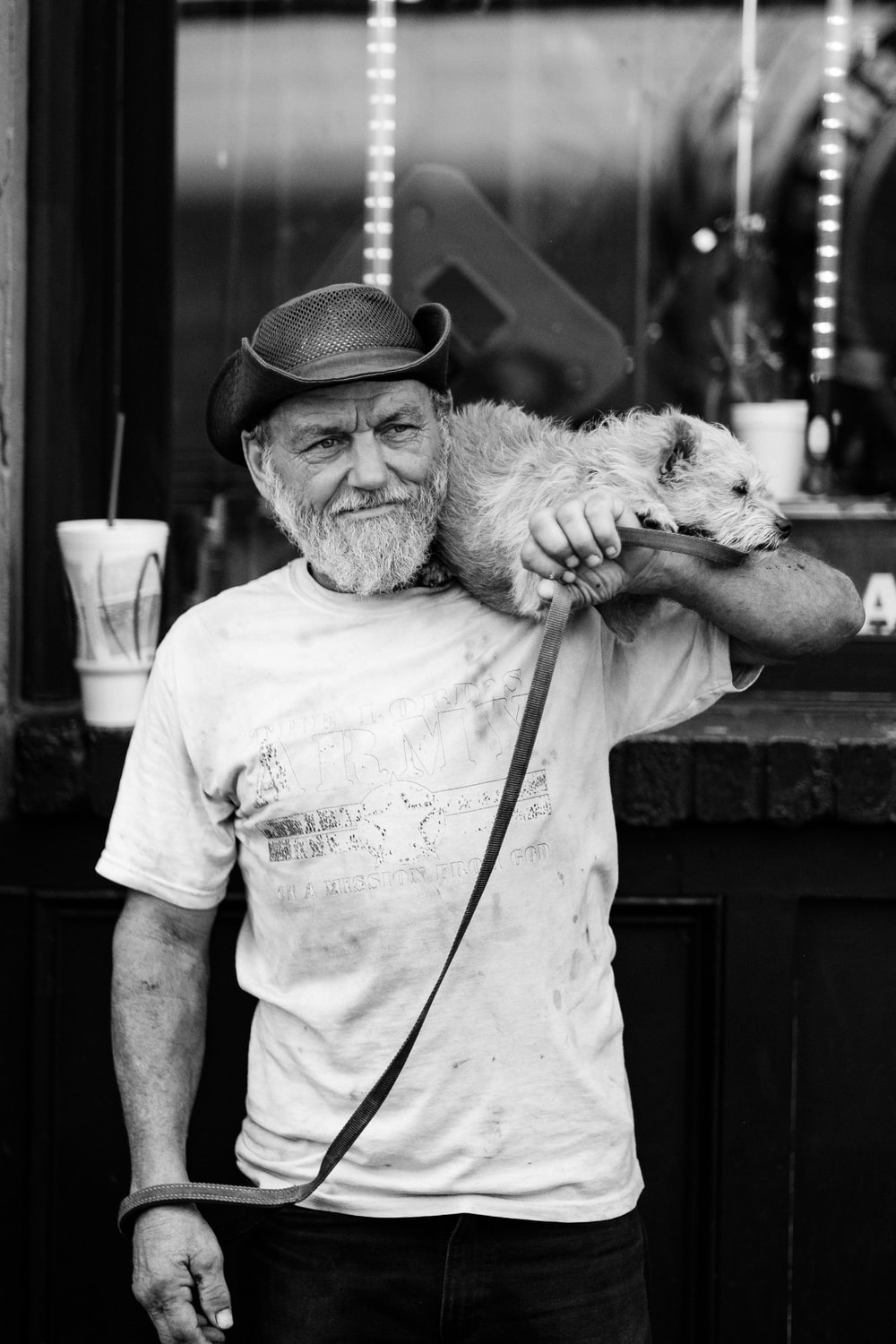 grayscale photography of a man carrying dog