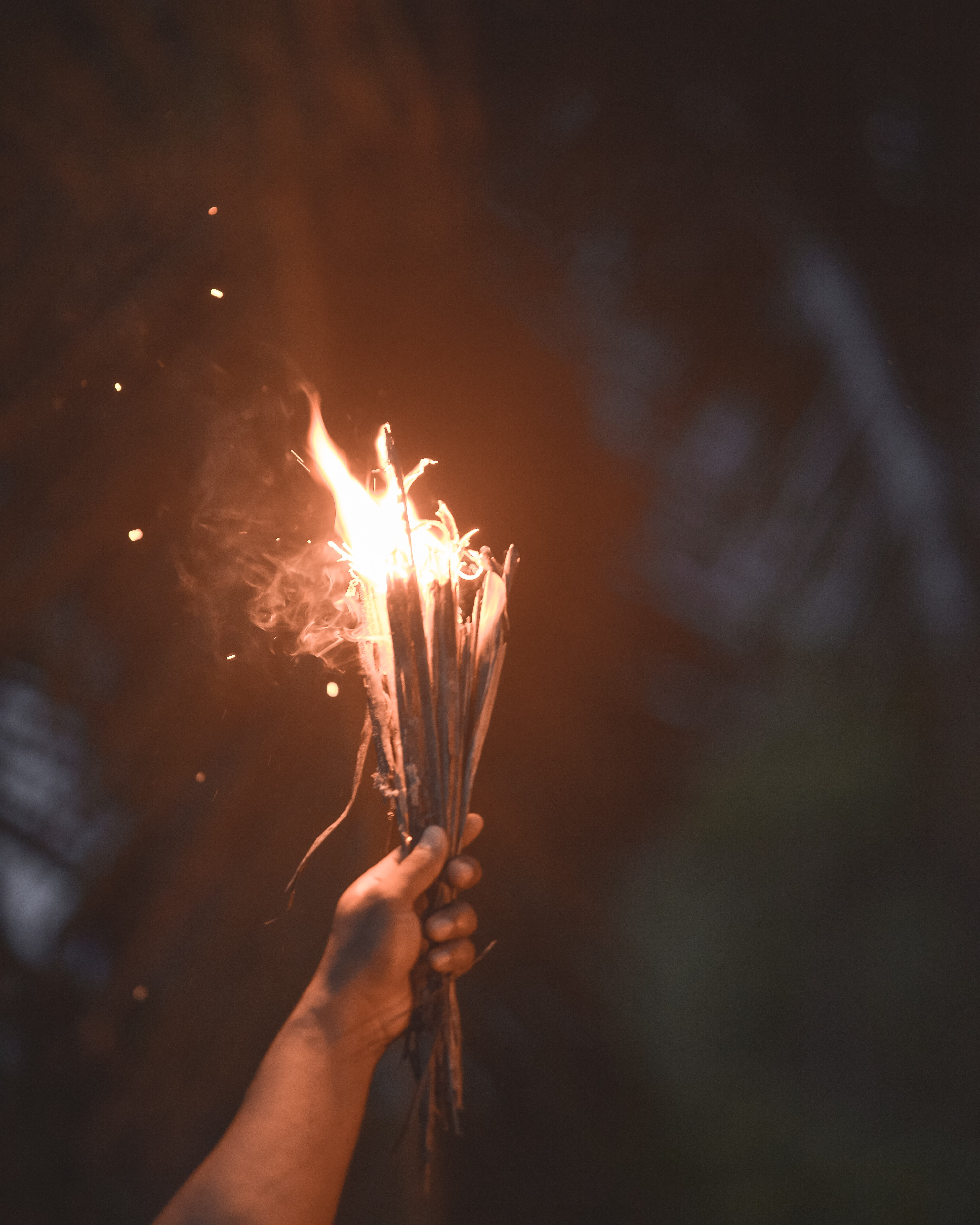 person holding burning sticks