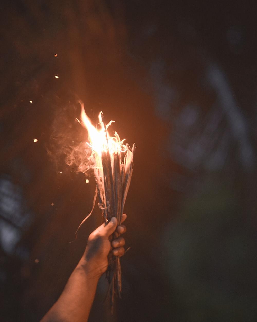 person holding burning sticks