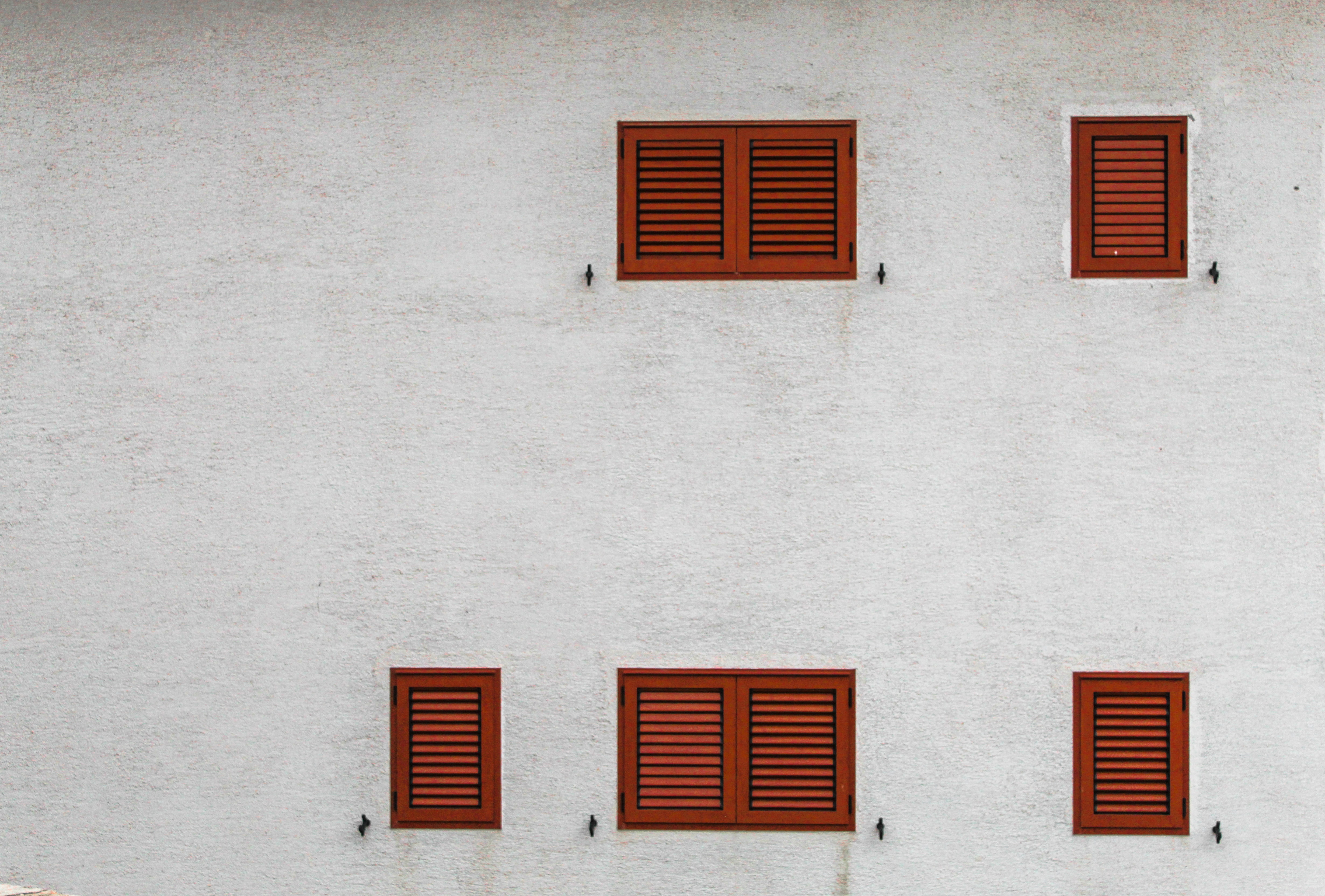 gray building with brown louvered windows