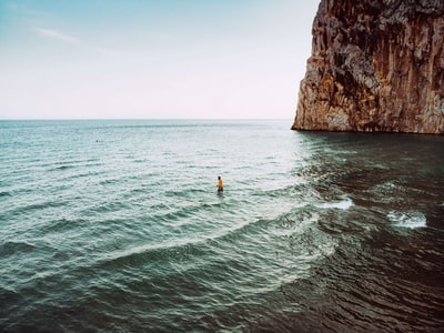 person on body of water beside rock