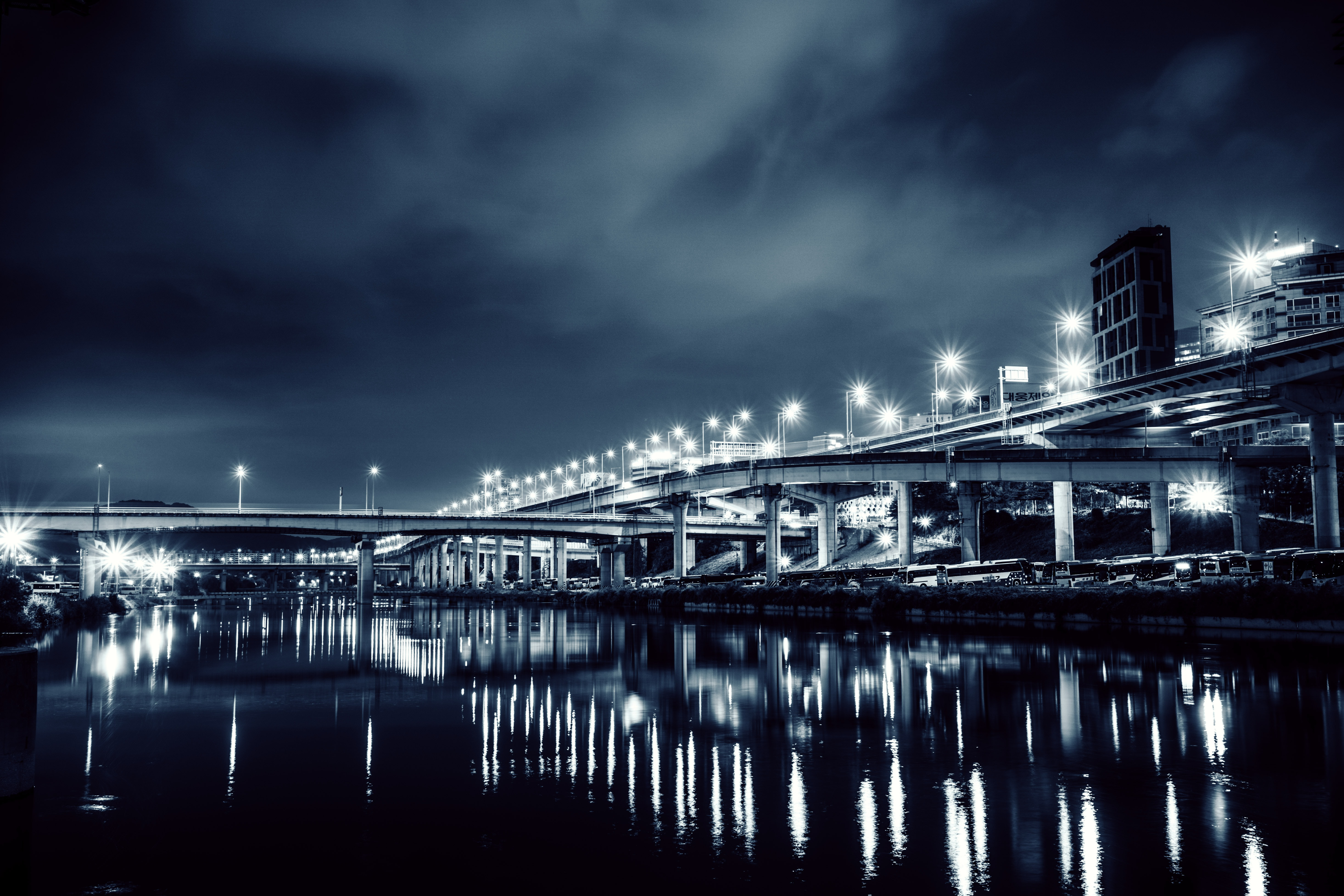 grayscale photography of bridge at night