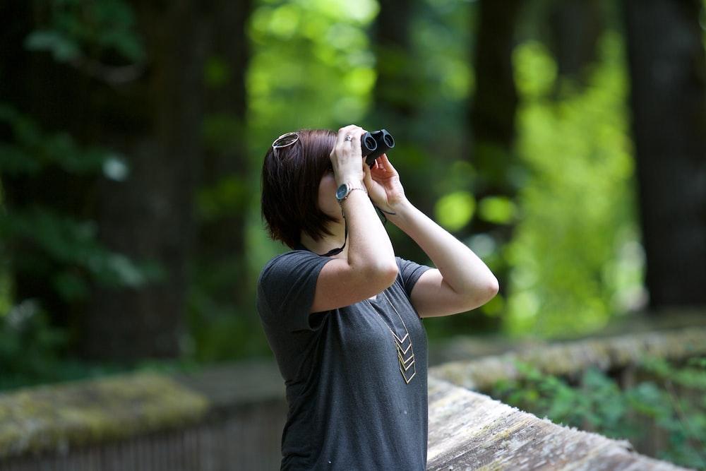 selective photography of woman holding binoculars looking upward outdoors