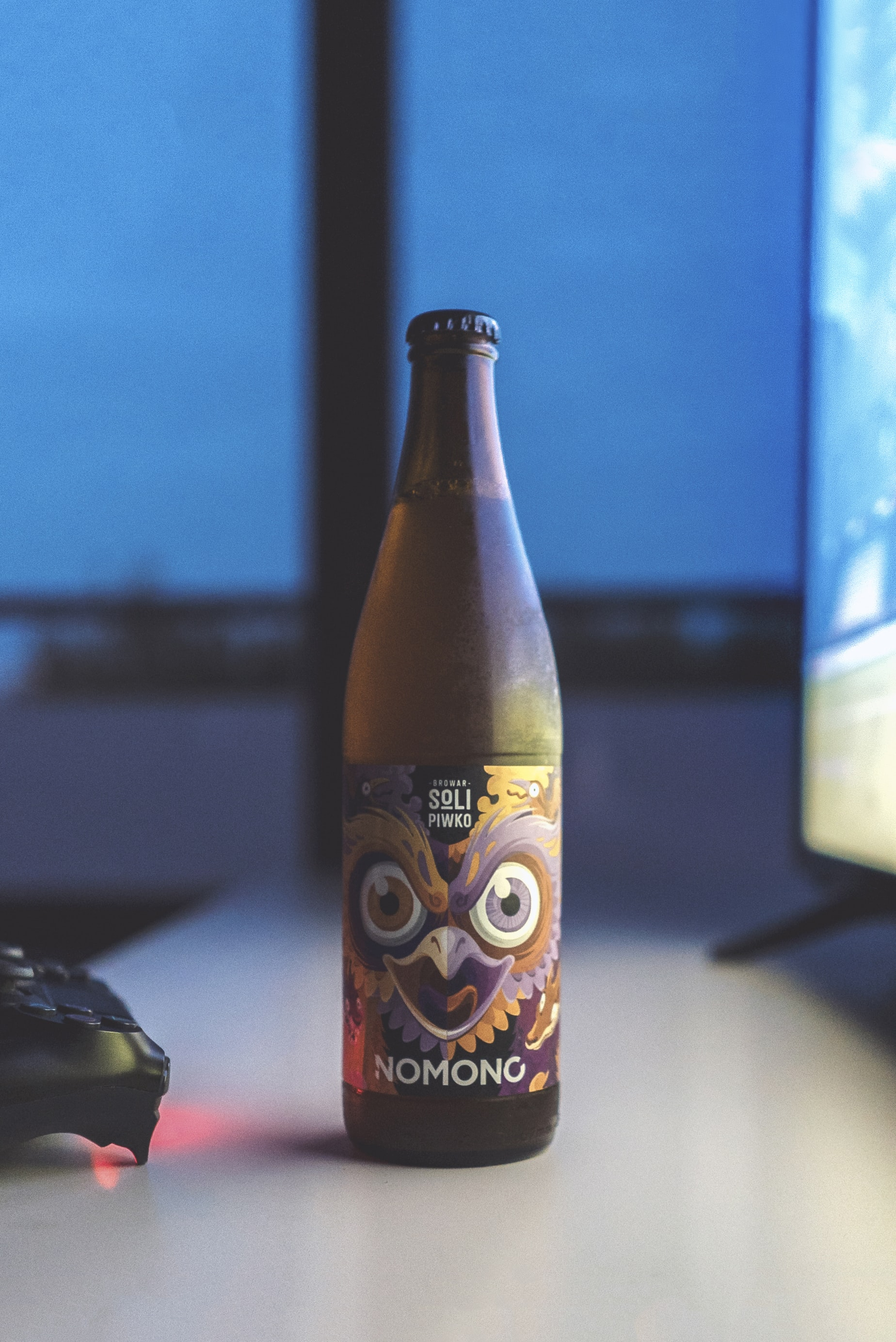 tilt-shift lens photography of Nomono beer bottle in-front of a flat screen TV