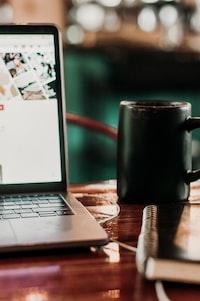 black ceramic mug beside laptop