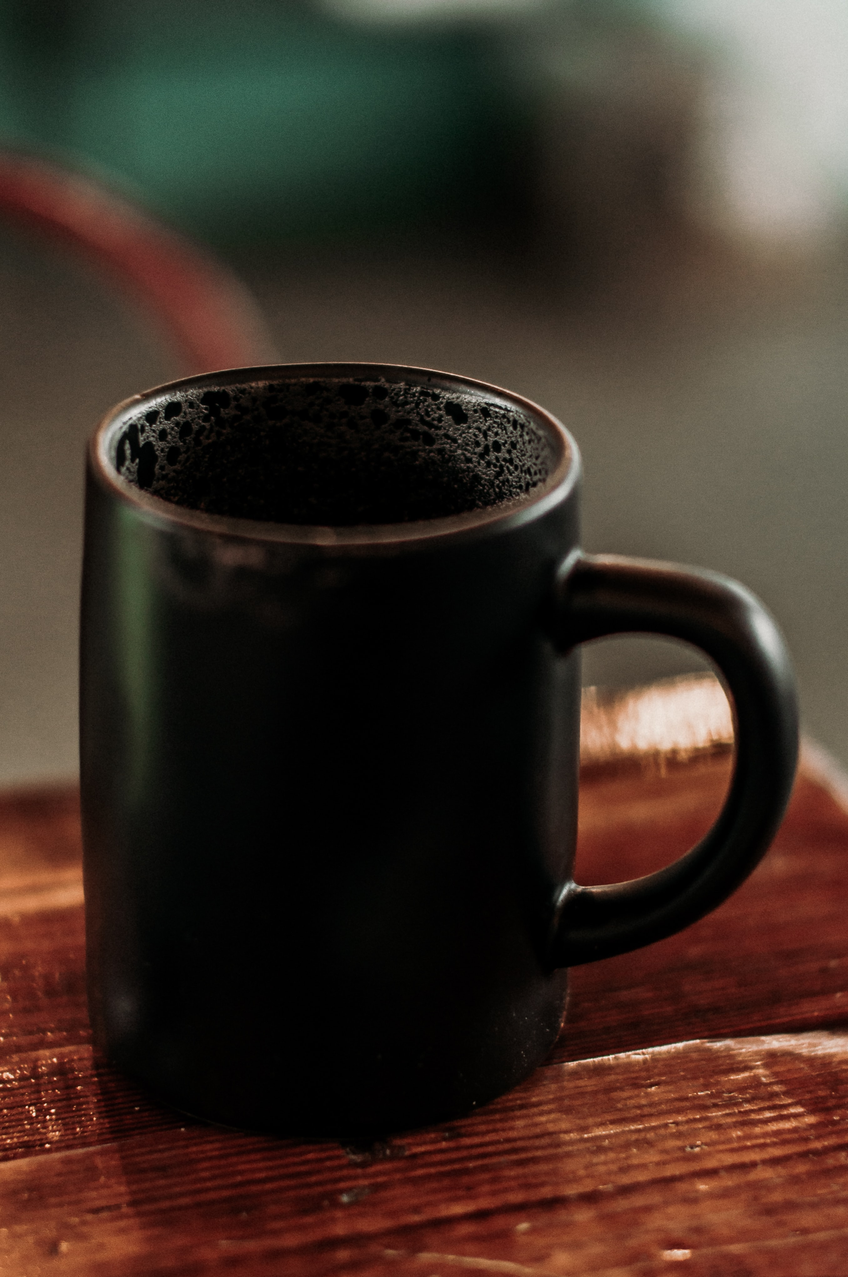 black ceramic mug on brown surface