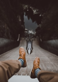 man in brown pants wearing low-top shoes in tilt shift photography