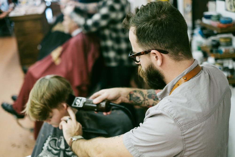 man shaving the boy's hair