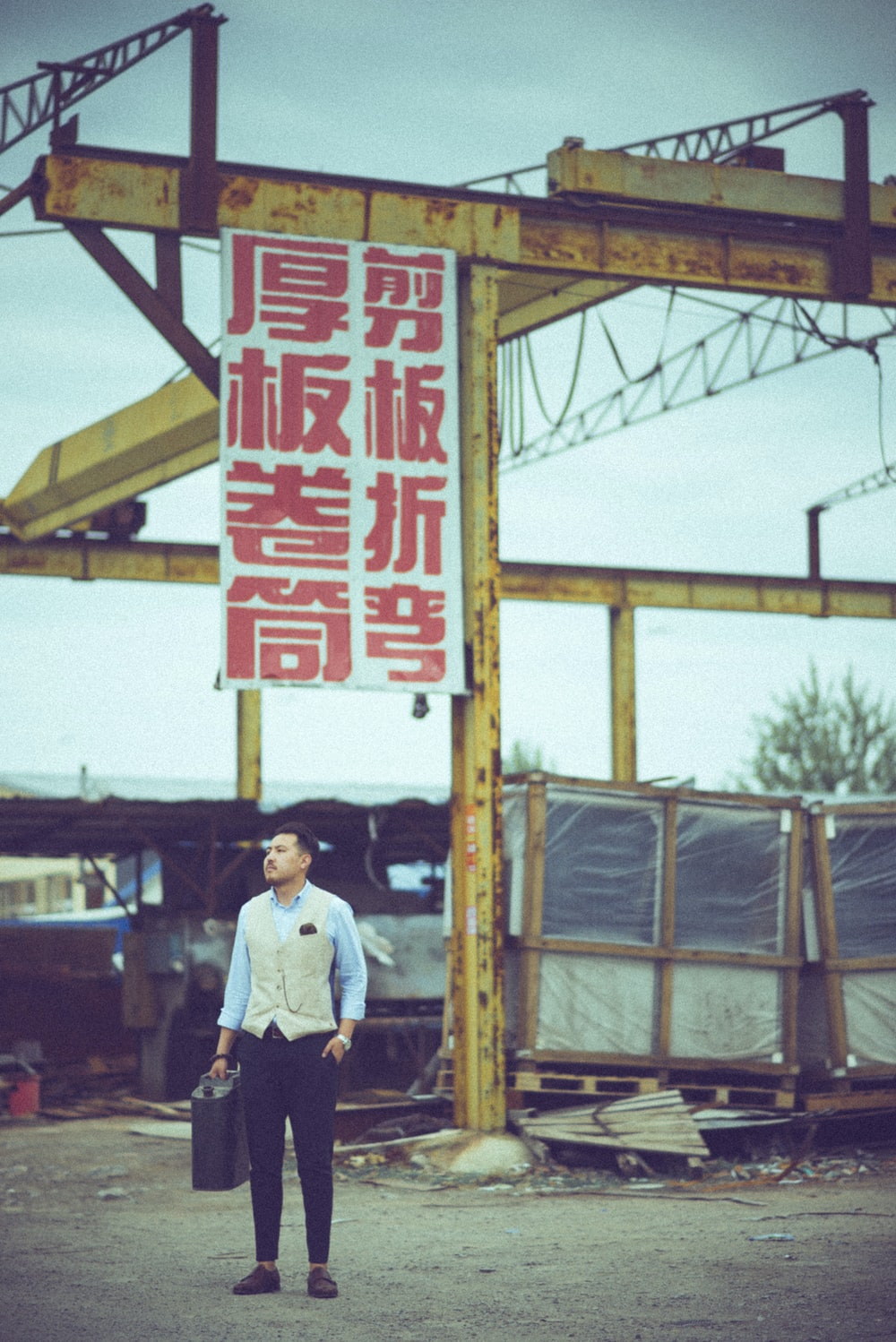 man carrying case standing near signage board