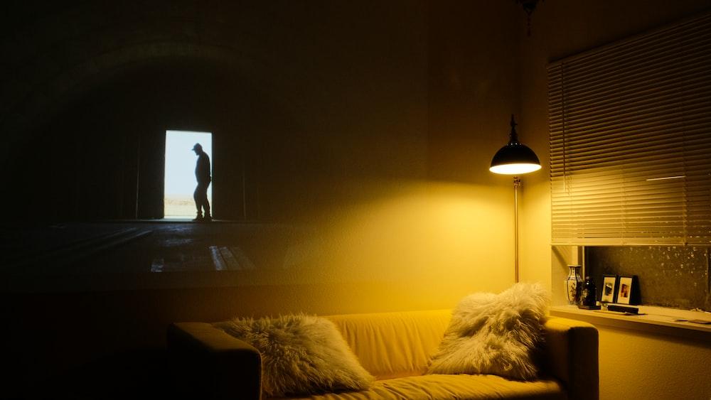 photo of beige padded sofa near floor lamp with window blind