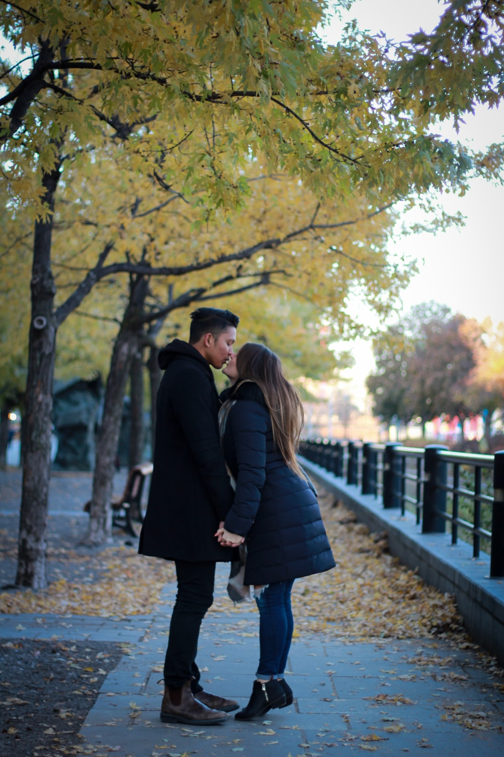 couple kissing in park under green leafed tree