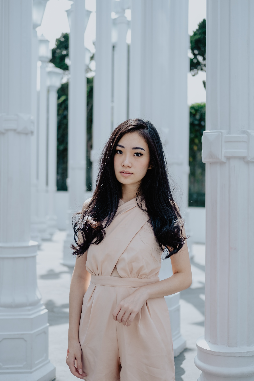 woman in peach-colored dress standing near pillars
