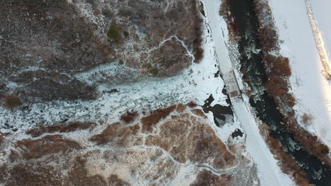 Top-down aerial view of a frozen waterfall, flowing into a turbulent river.