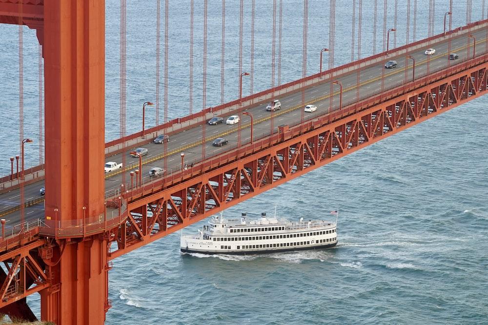 white cruise ship under concrete bridge