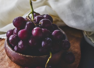 photography of red grapes on bowl