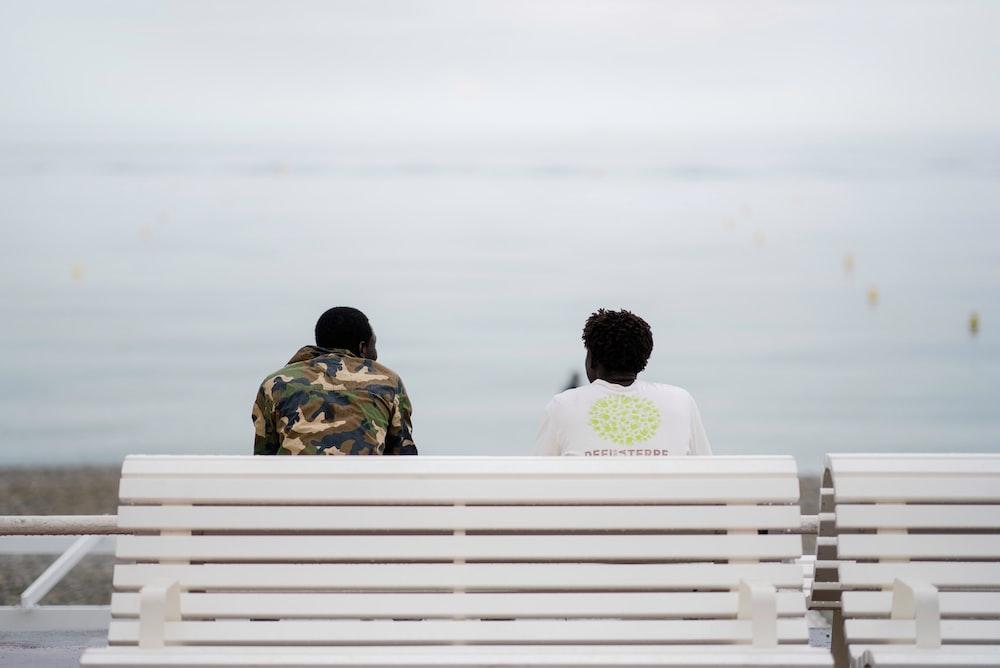 two men sitting on bench facing sea