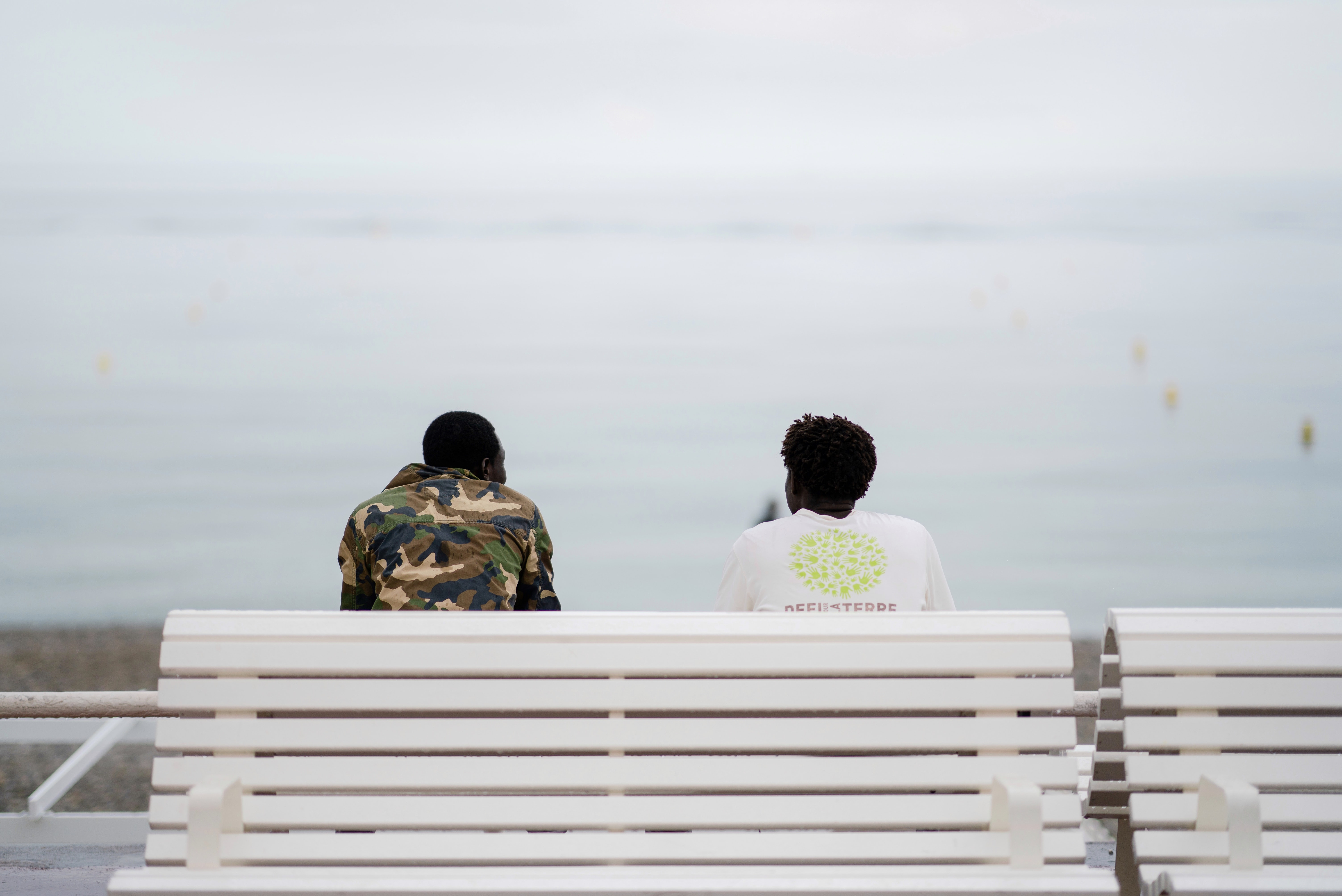 two men sitting on bench facing sea