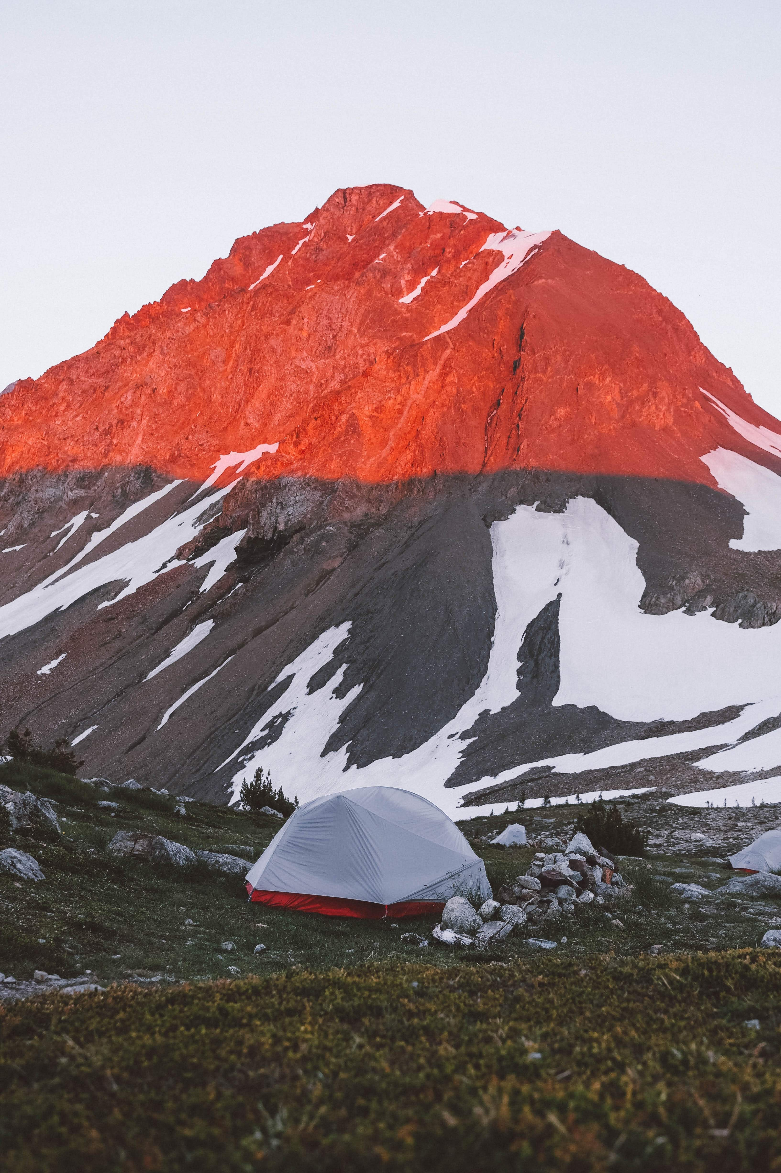 white and red camping tent near mountain