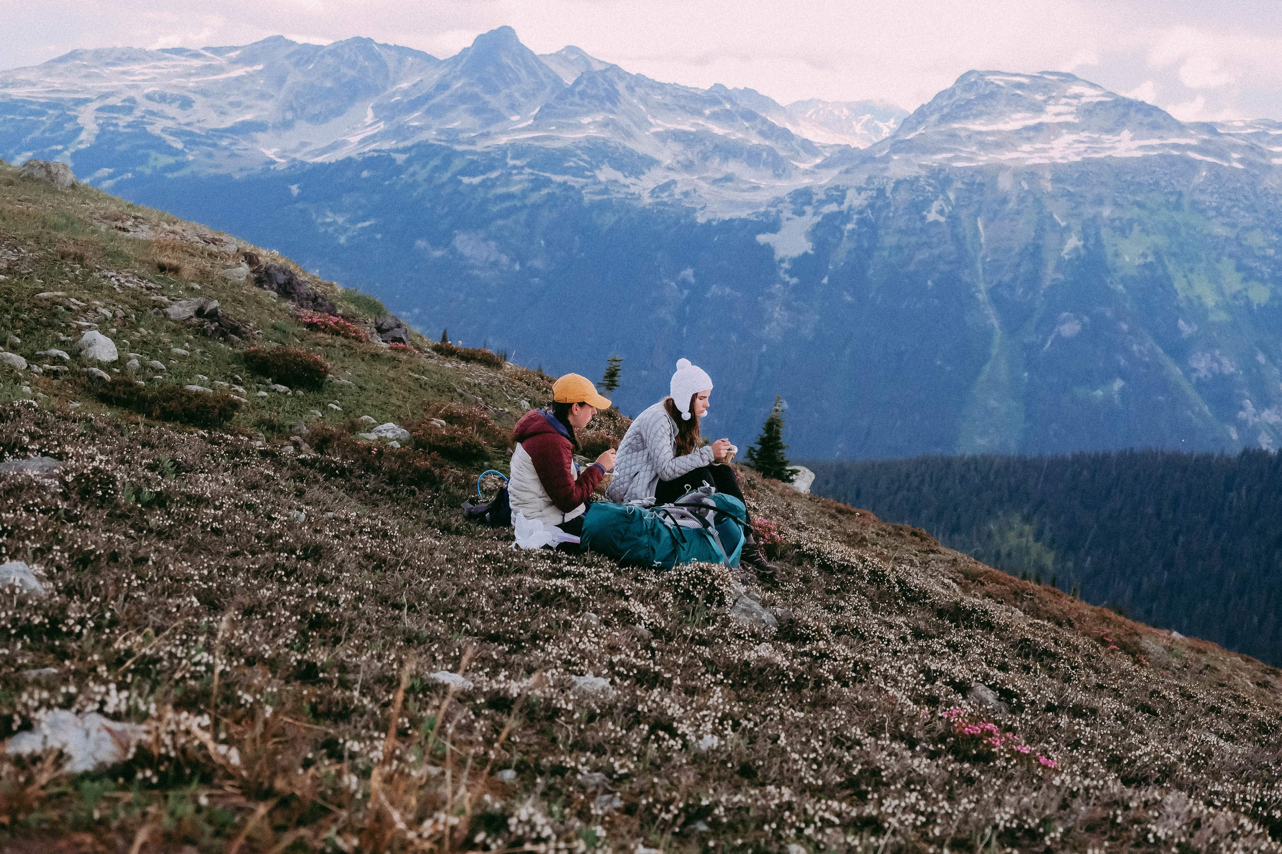man and woman sitting on ground looking at mountain