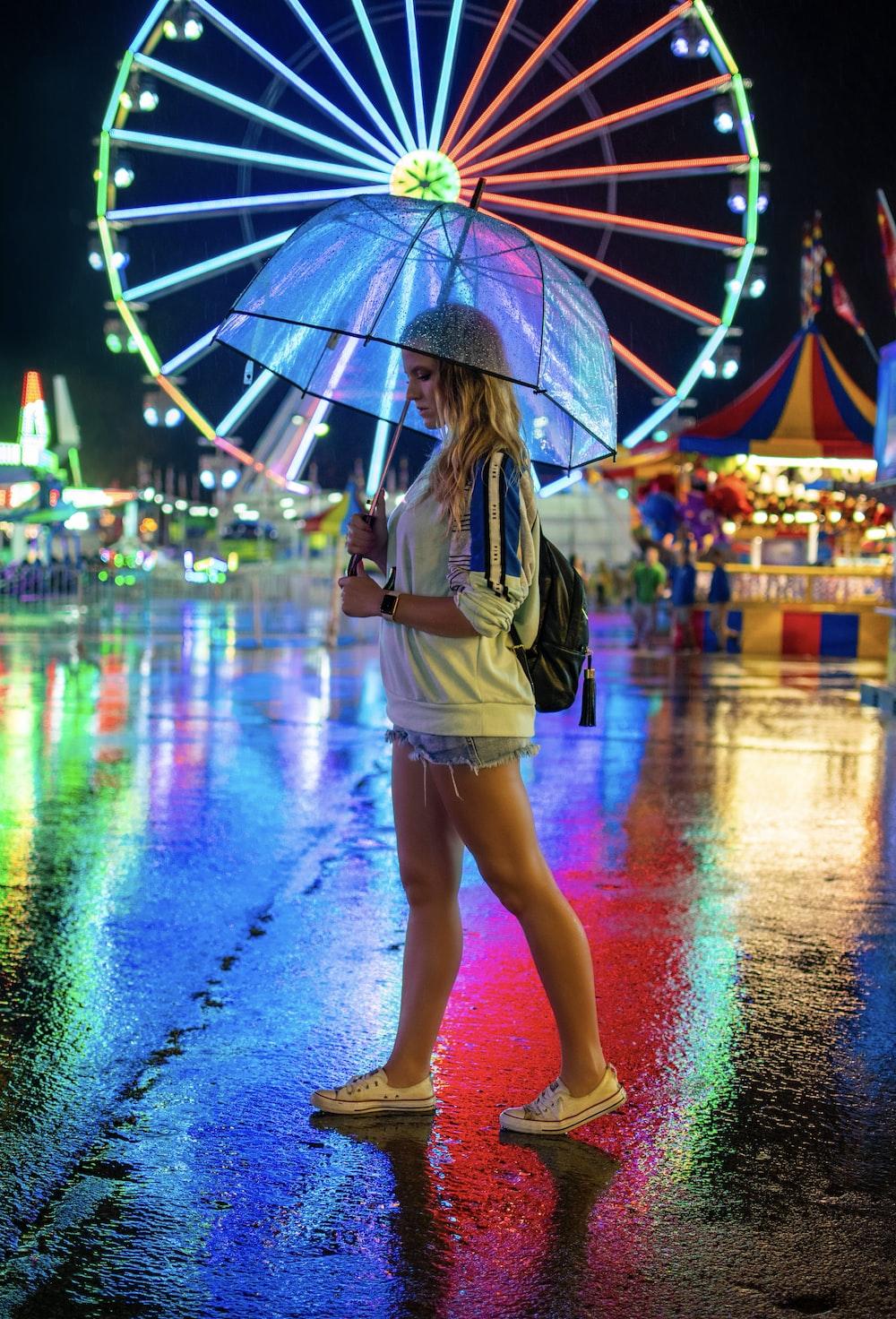 woman walking on pavement holding umbrella