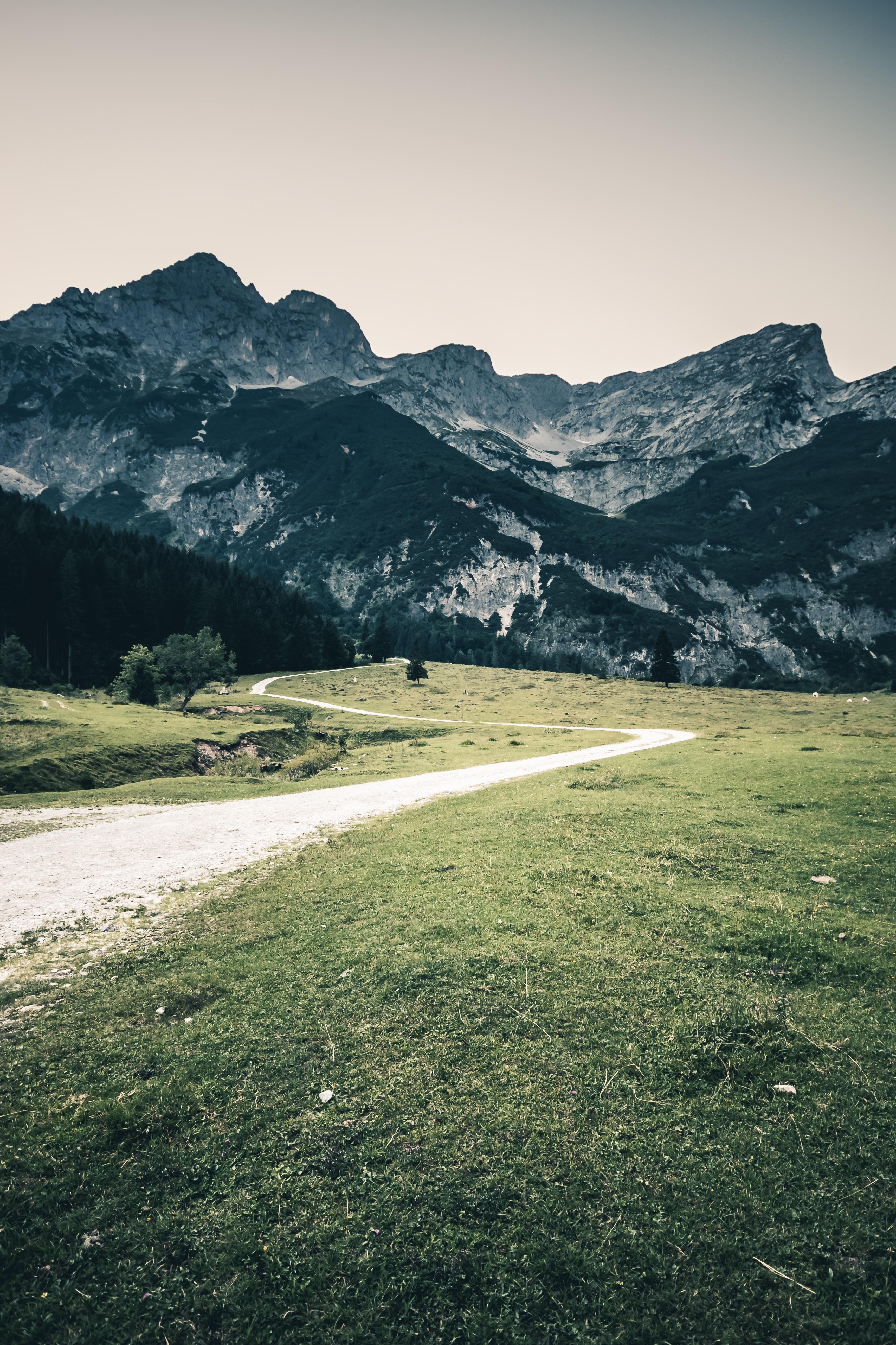empty curvy road near black mountain at daytime