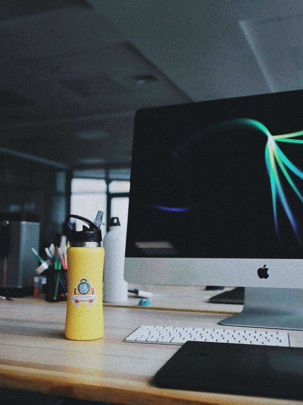 powered on silver iMac beside yellow tumbler