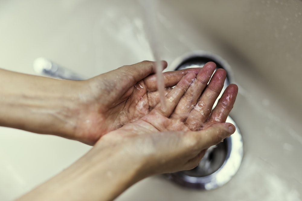 person washing hands over sink