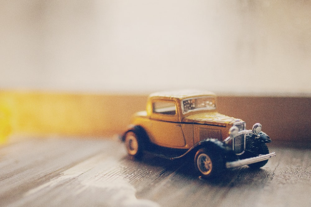 selective focus photography of classic brown coupe die-cast model on gray ground