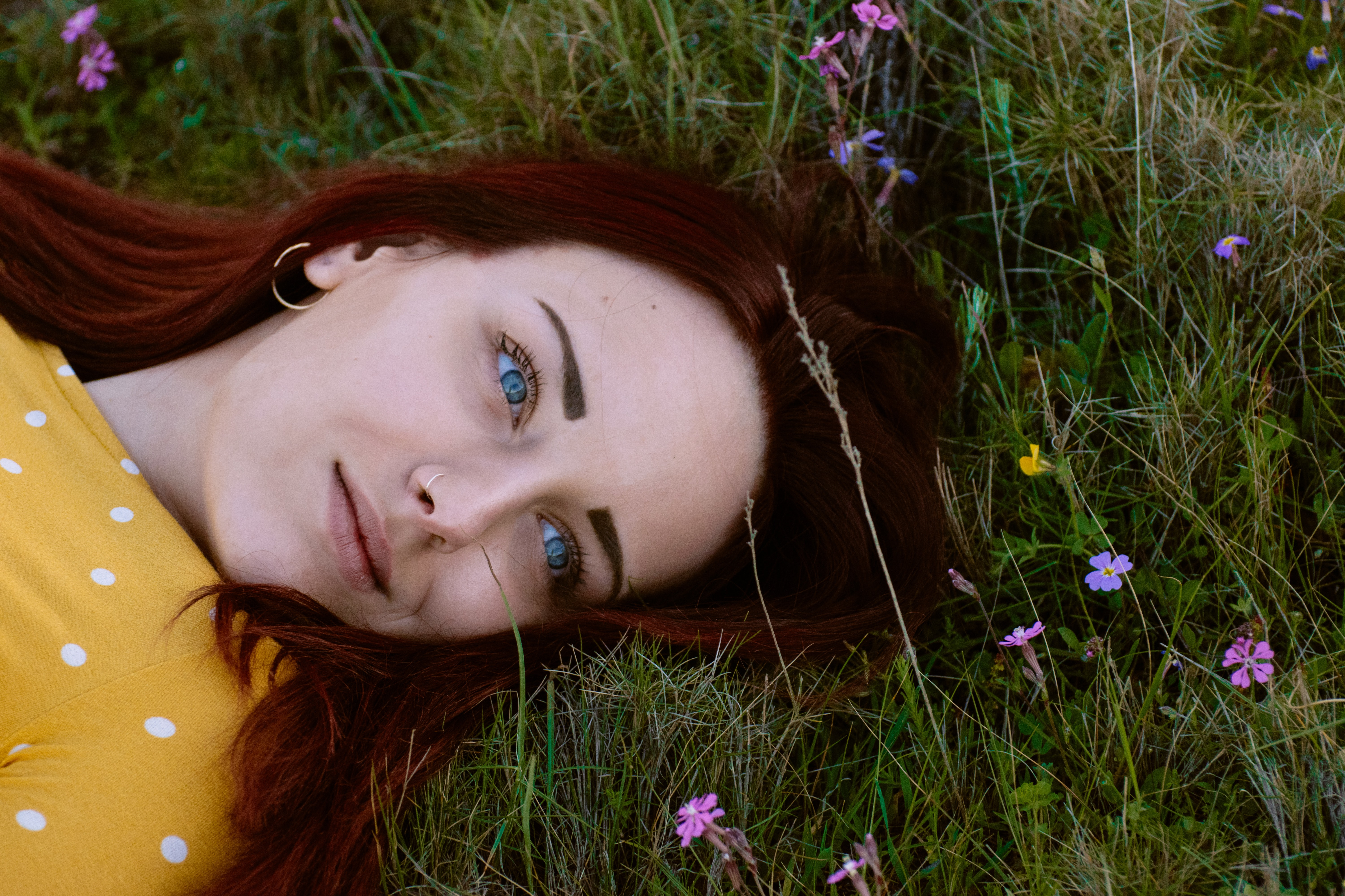 woman in brown and white polka-dot top lying in green grass during daytime