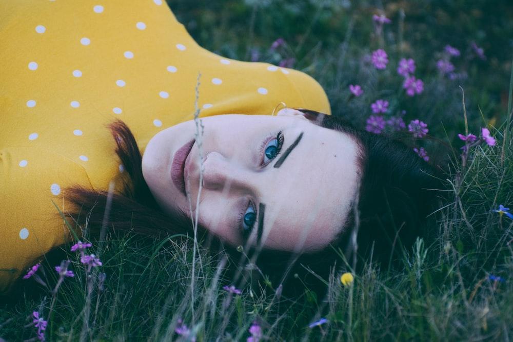 woman lying on green grassy field