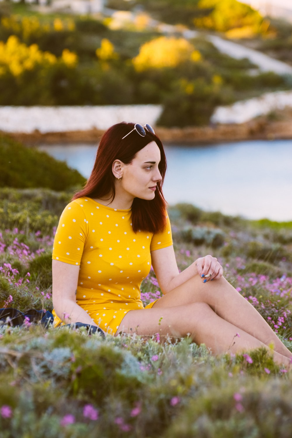 woman sitting on green grass while looking sideways
